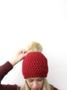 Crochet hat with faux-fur pom-pom.